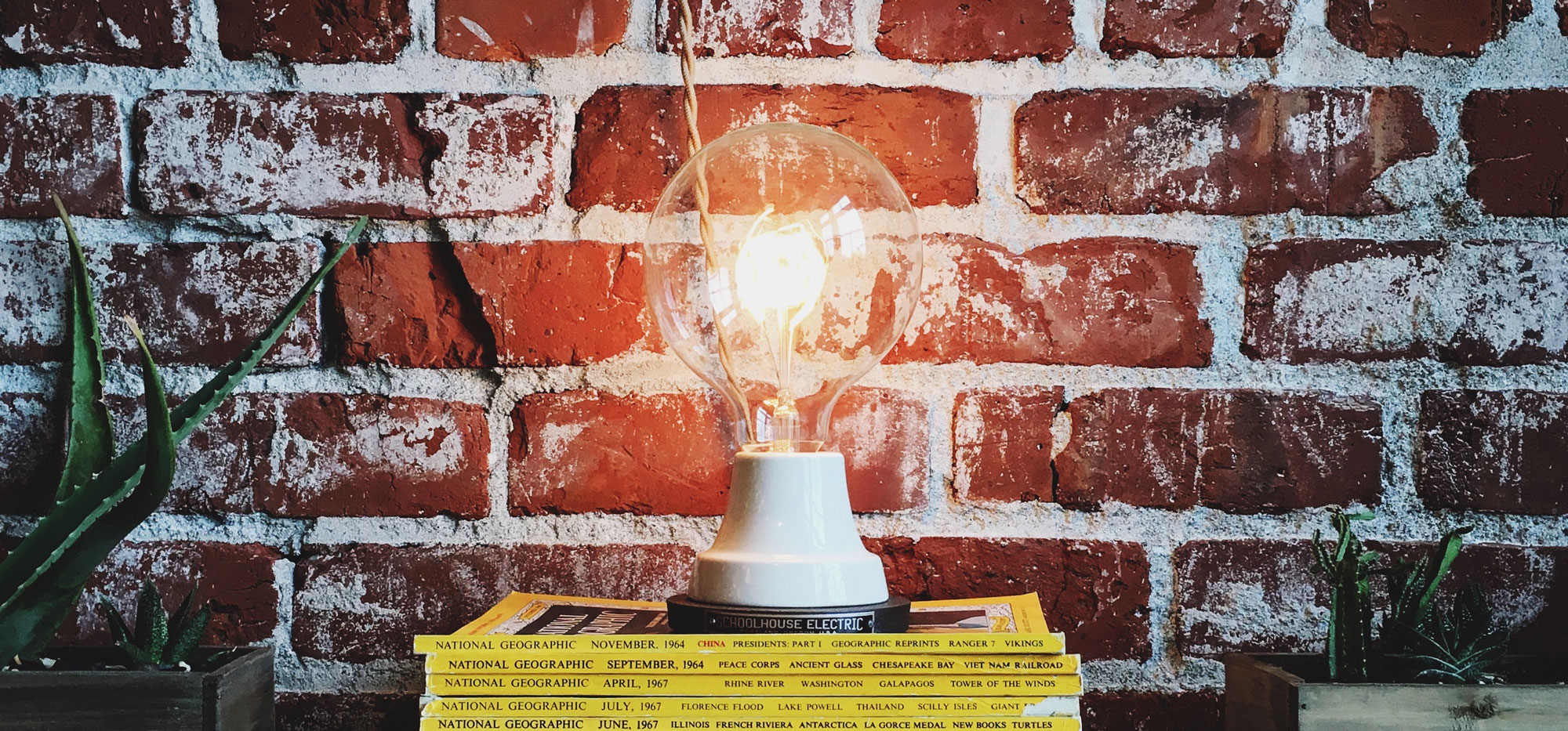 A lightbulb resting on a pile of magazines